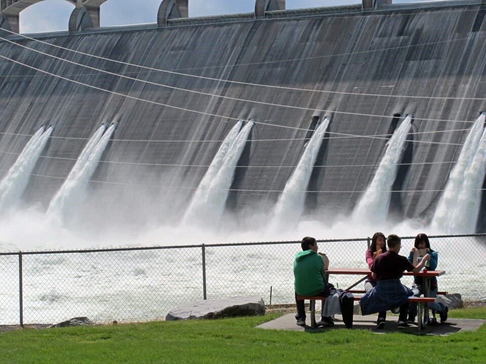 Students eat at a table in front of the impressive Grand Coulee dam, on the Columbia river. The valves are leaking a large amount of water.