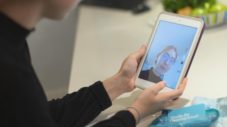Elle regarde une photo d'elle sur un iPad.