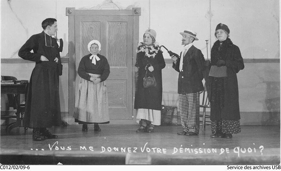 Photo en noir et blanc montrant cinq comédiens de la pièce Bibi. Ils sont tous costumés.