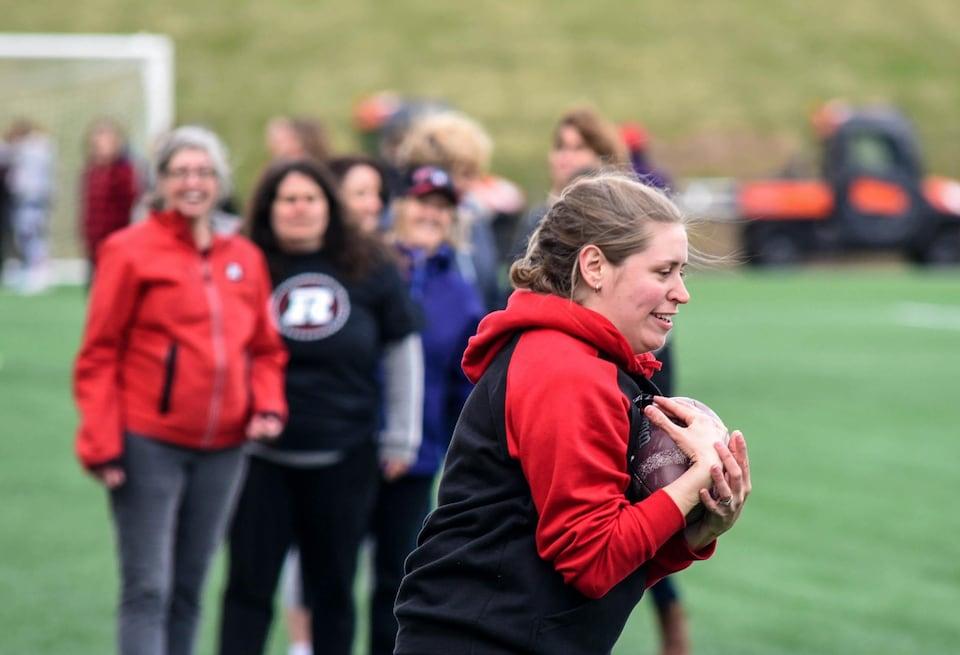En avant-plan, une femme tient un ballon de football collé contre elle, avec en arrière-plan un groupe de femmes qui sourient en la regardant.