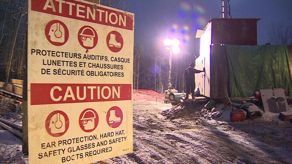 Site de forage, avec panneau d'avertissement et cabanes en bois.