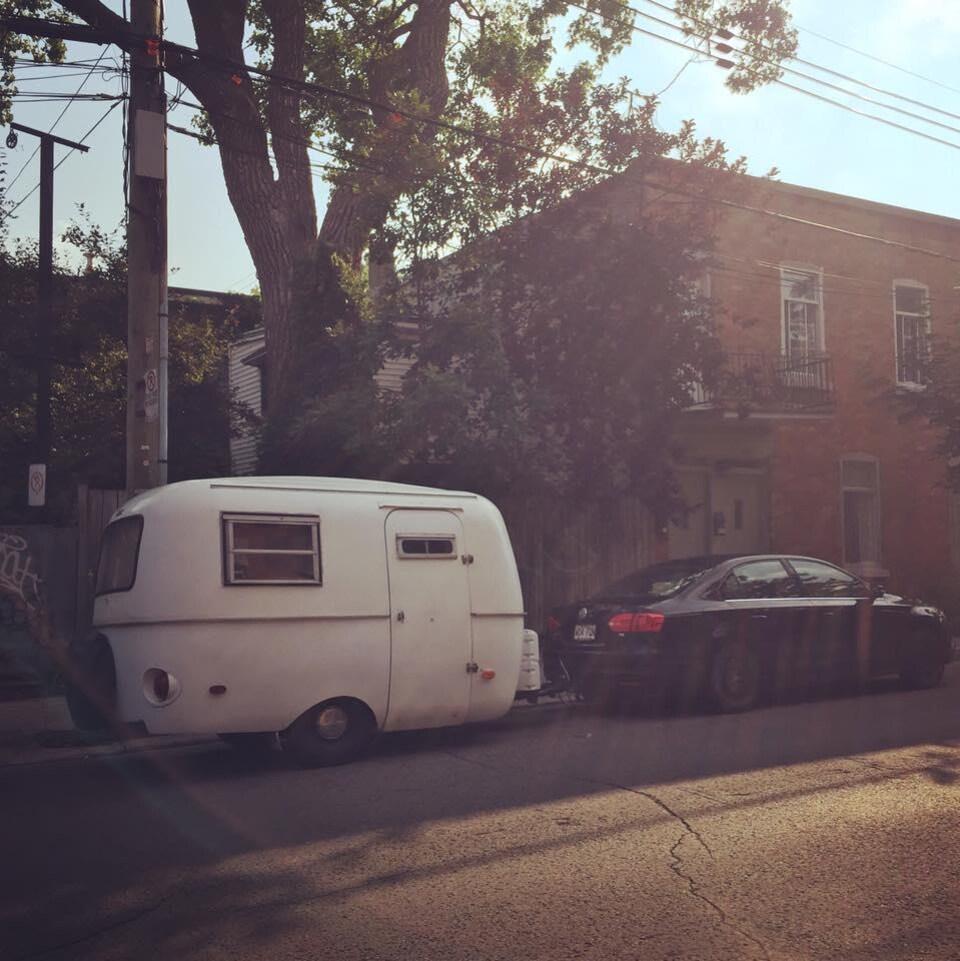Une petite roulotte derrière une voiture noire.