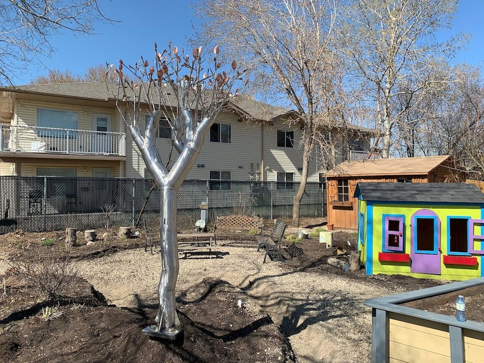 La sculpture est au milieu d'un jardin qui ressemble à un parc. Une maisonnette pour enfants et un cabanon se trouvent d'un côté. Une table à pique-nique se trouve derrière.