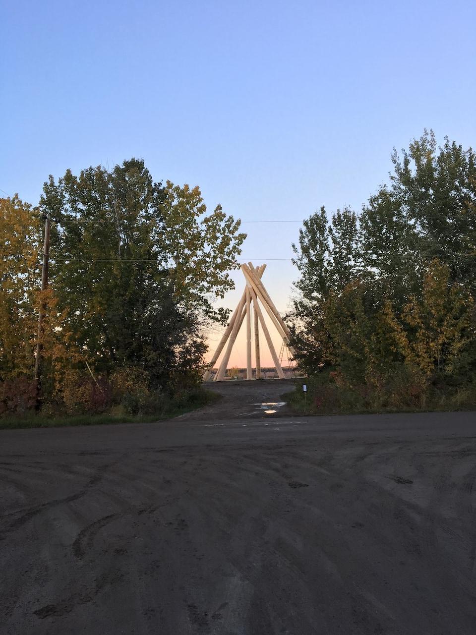Une installation autochtone devant un coucher du soleil.