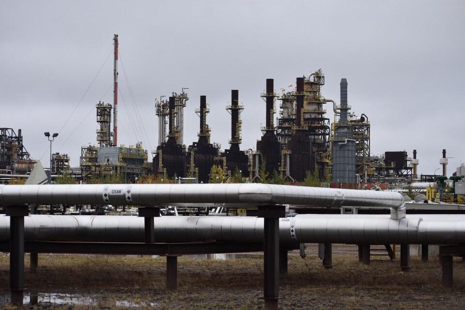 Des tuyaux gris font face à des installations pétrolières.