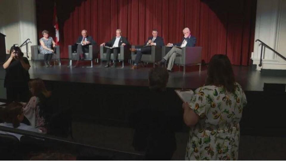 Une femme de dos tient une feuille de papier et d'adresse à quatre hommes et une femme assis sur une scène devant un rideau rouge.
