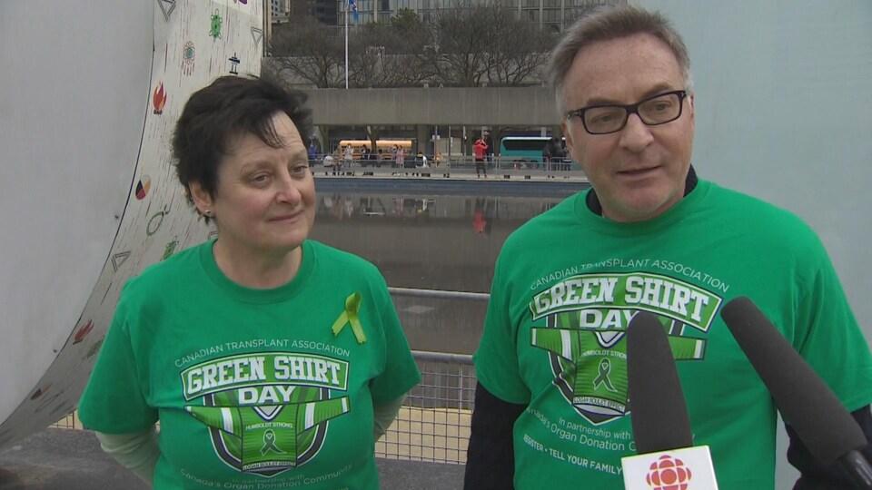 Une soeur et son frère, vêtus de chandails verts, répondent au micro de Radio-Canada.