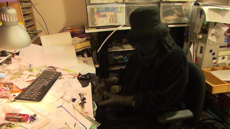 Une femme couverte de noir est assise devant une table d'ordinateur ensevelie sous une montagne de papiers.