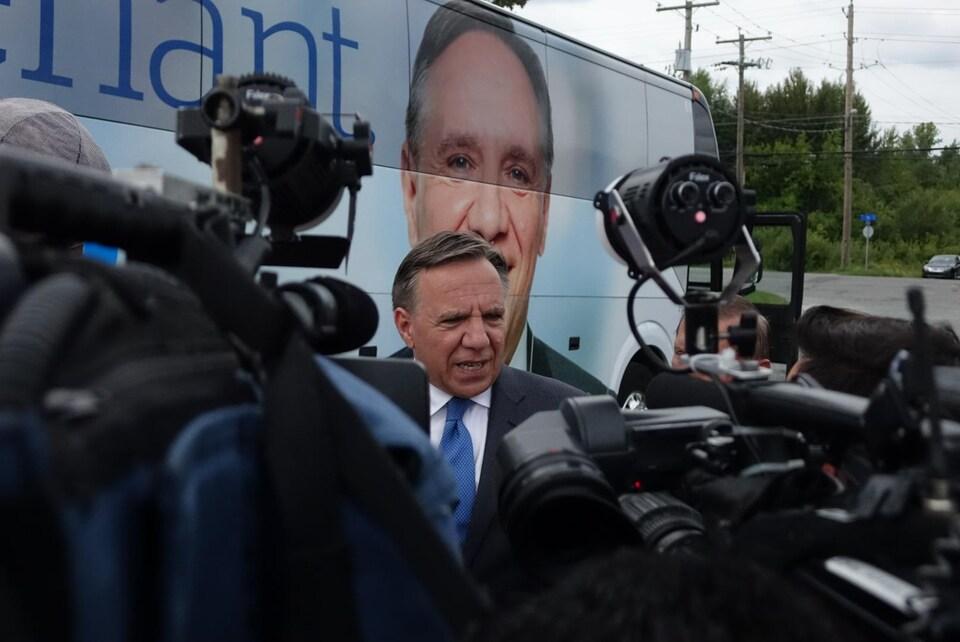 François Legault, chef de la Coalition avenir Québec, est entouré de caméras pendant qu'il parle aux médias devant son autobus de campagne.