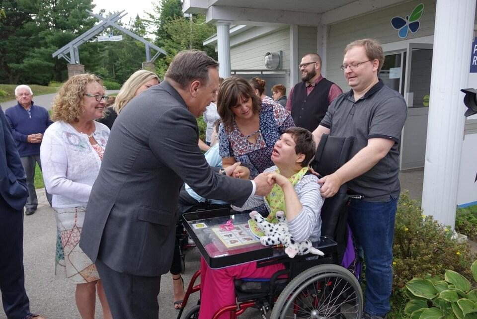 François Legault salue une jeune fille handicapée.