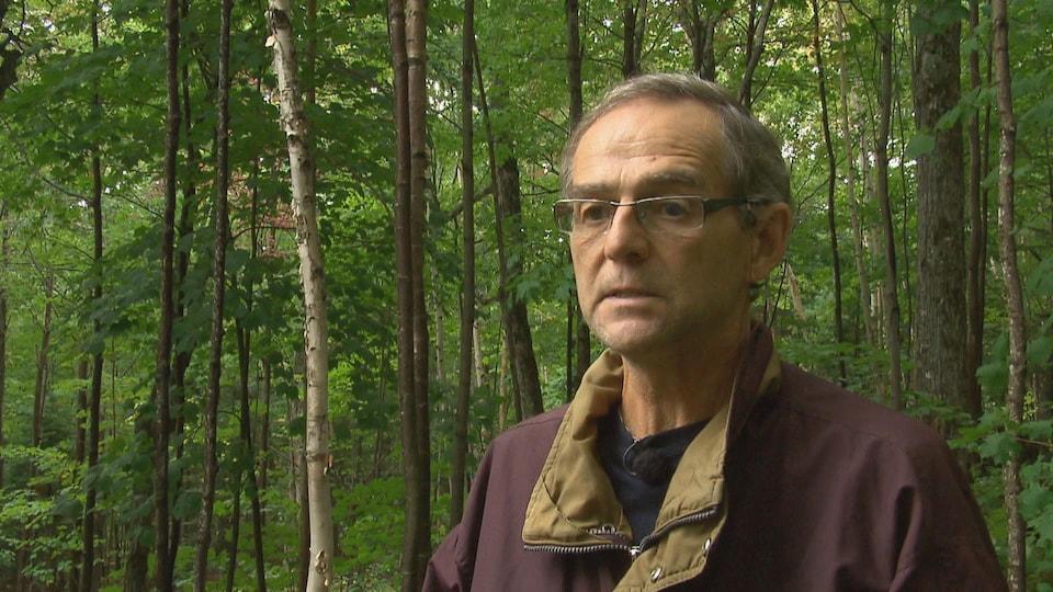François Lessard accorde une entrevue au journaliste de Radio-Canada Alexandre Duval dans le secteur où auront lieu les coupes. On aperçoit des arbres feuillus derrière lui.