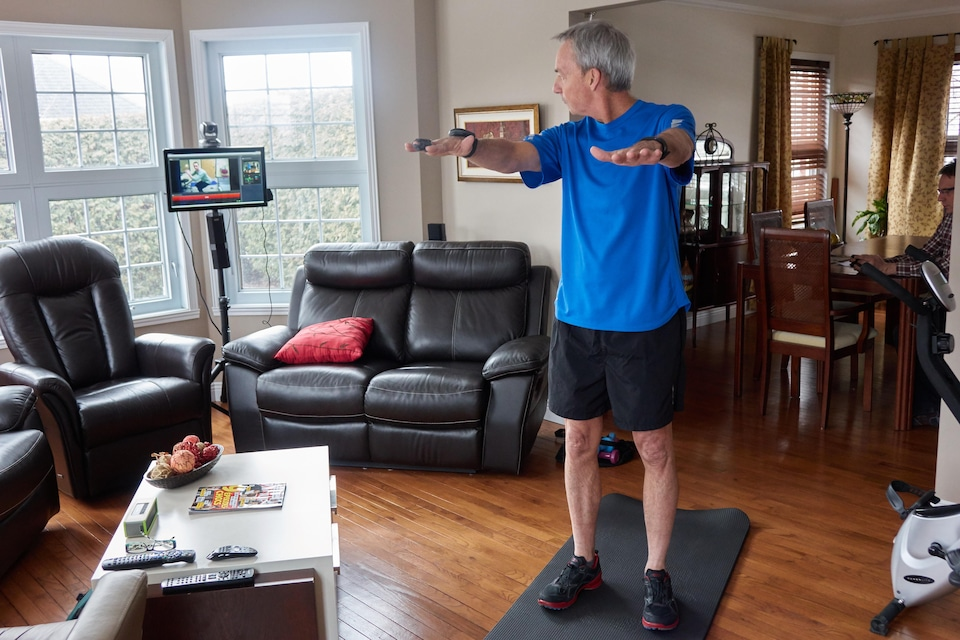 Frédéric Grenier dans son salon regarde l'écran où apparaît en direct son physiothérapeute.