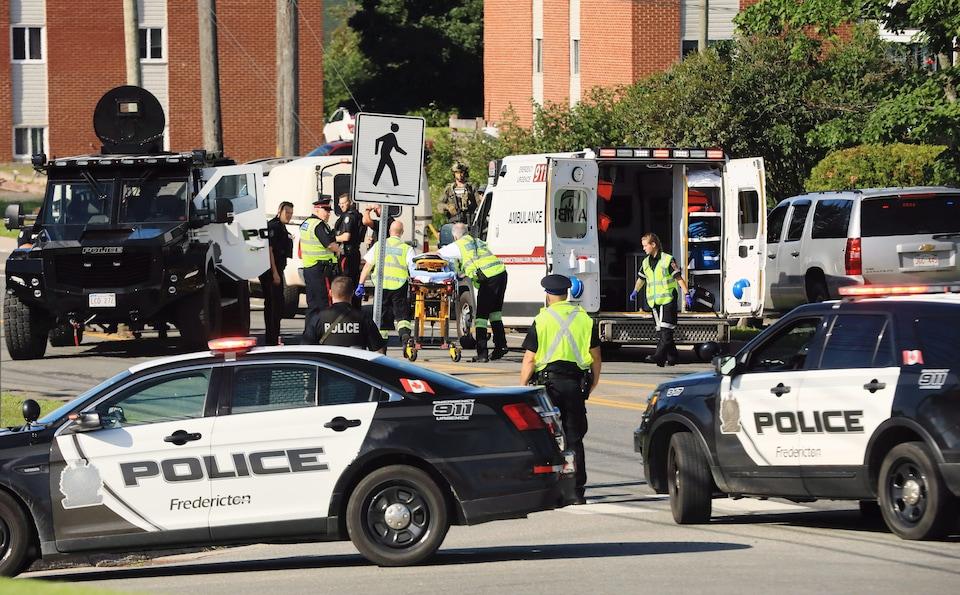 Des policiers et des ambulanciers paramédicaux sur les lieux de la fusillade à Fredericton