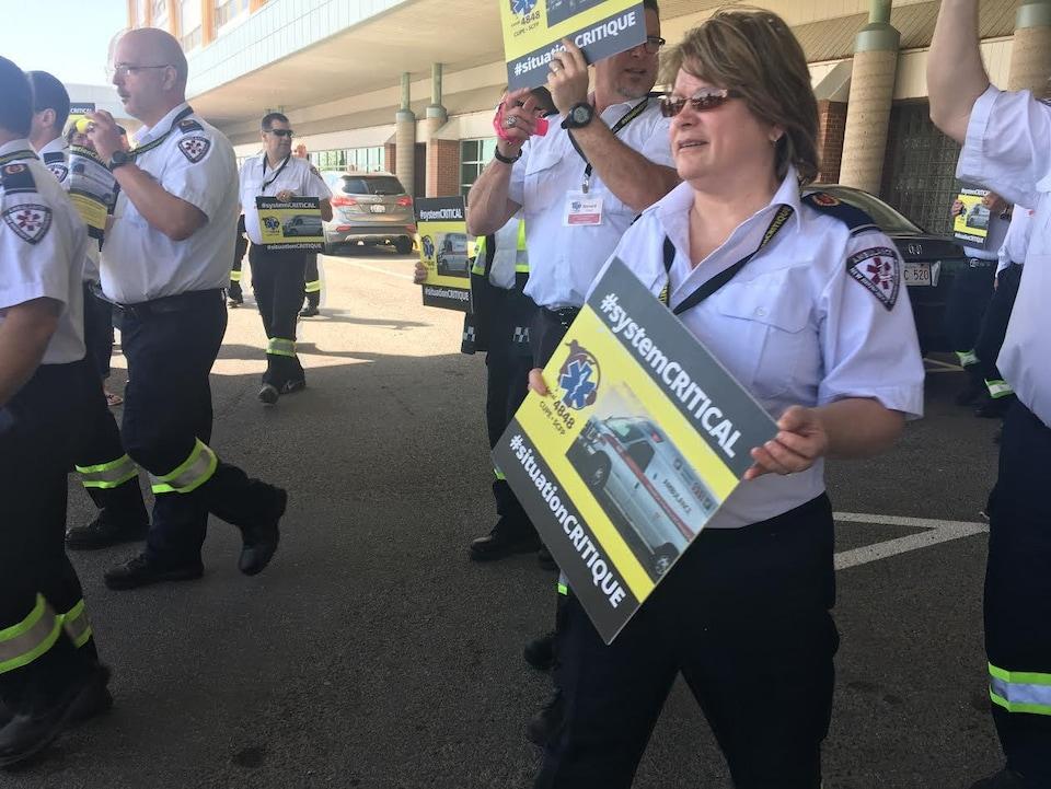 Des ambulanciers en uniforme marchent devant un hôpital en brandissant des pancartes syndicales.