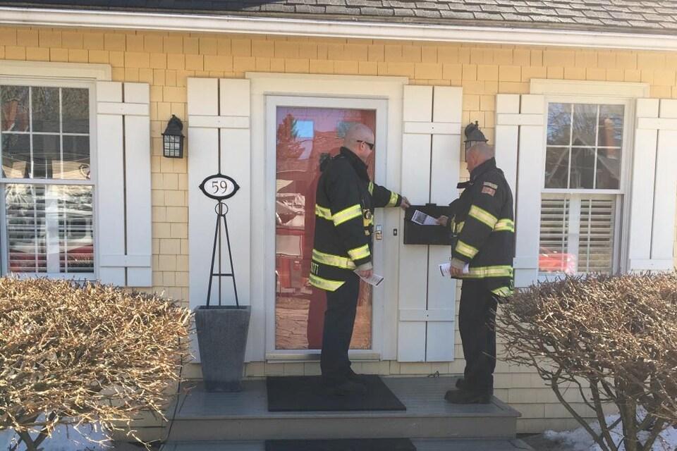 Deux pompiers déposent un feuillet d'information dans la boîte de courrier d'une maison.