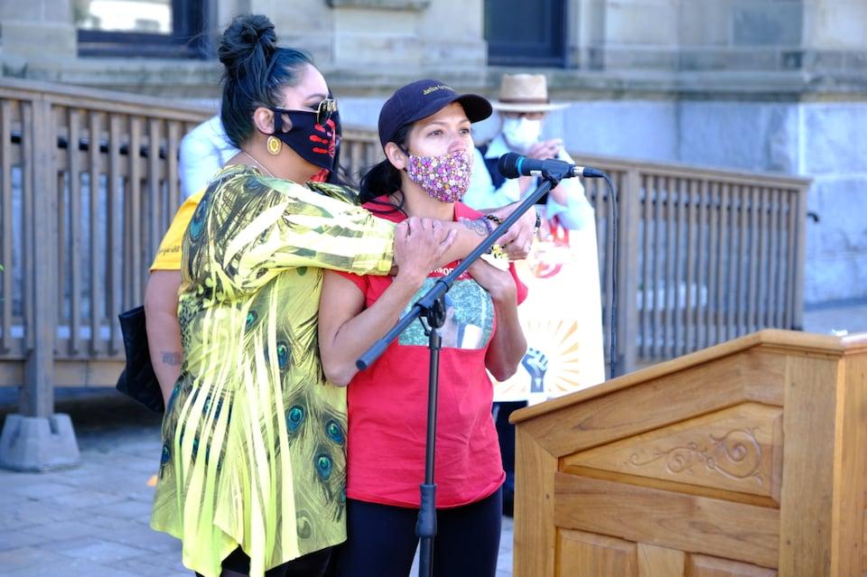Une femme enlance une autre femme qui parle au micro lors d'un rassemblement à l'extérieur.
