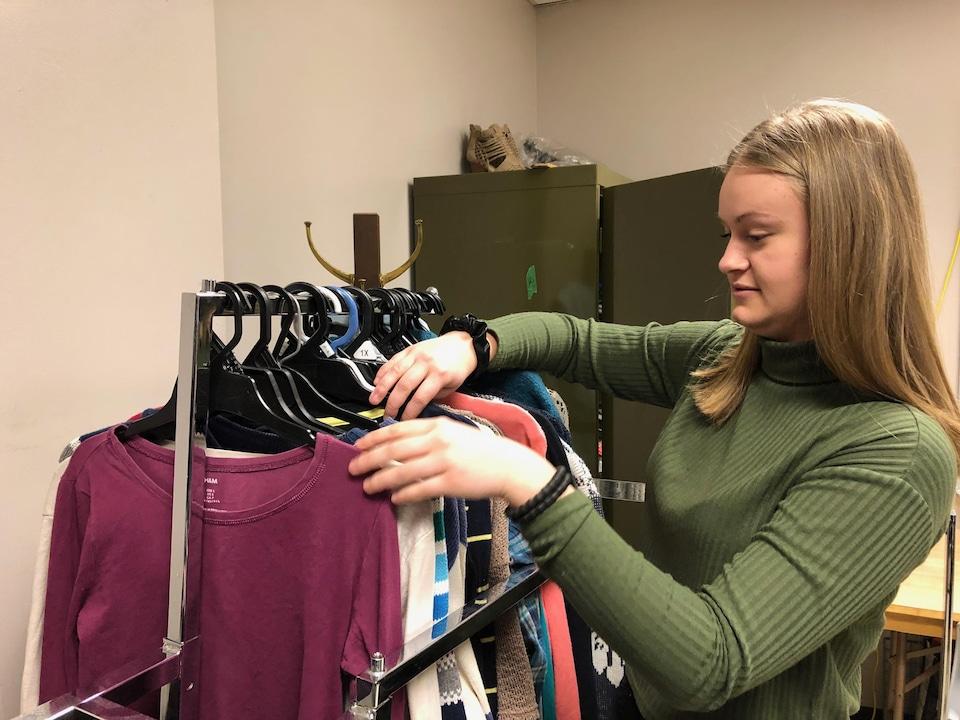Une adolescente regarde un présentoir à vêtements.
