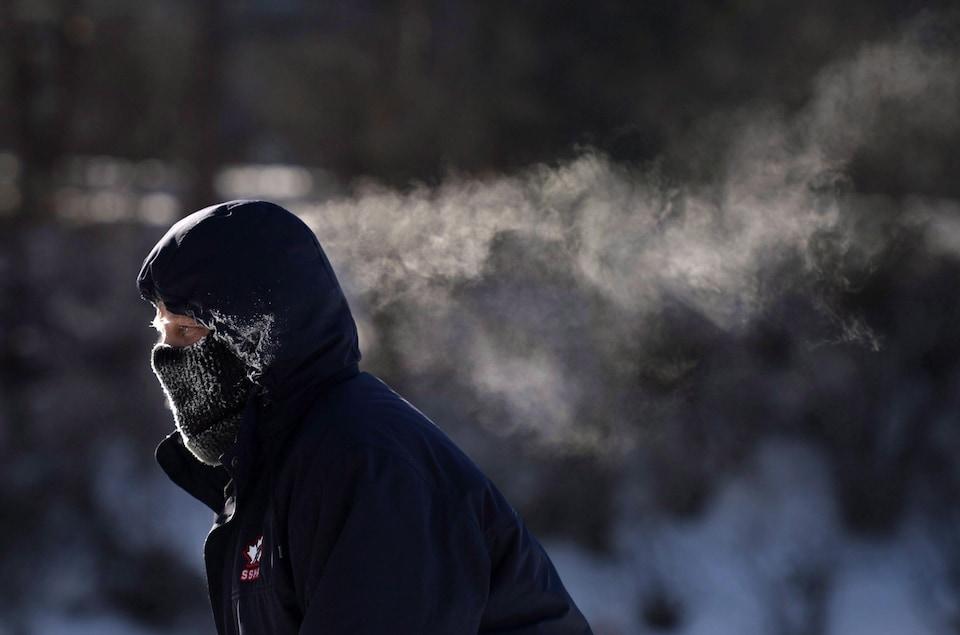 La respiration d'un patineur fait des traînées de condensation derrière lui.