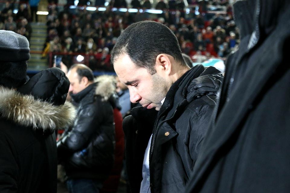 Un homme pleure pendant les funérailles des victimes de la tuerie de Québec, à l'aréna Maurice-Richard.