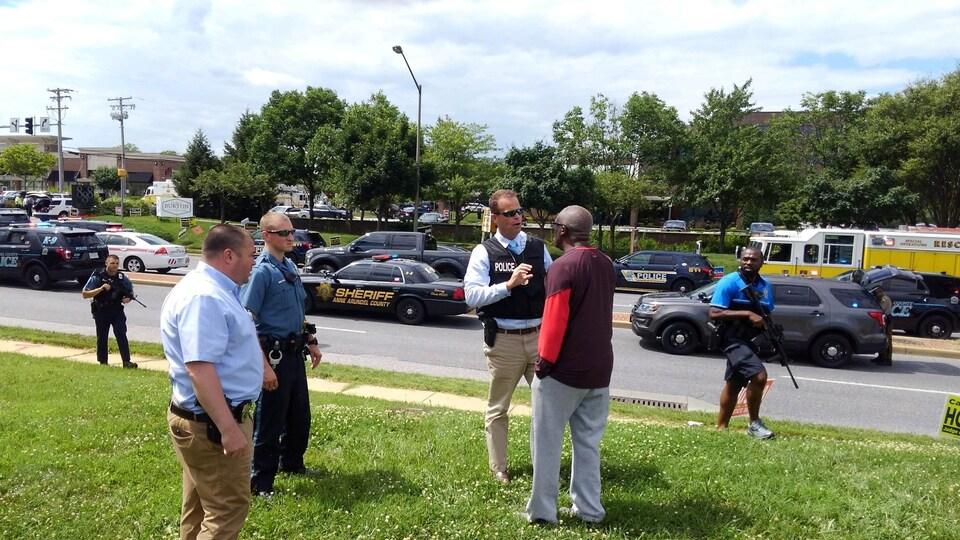 Des policiers interrogent un homme près du lieu de la fusillade à Annapolis, au Maryland.