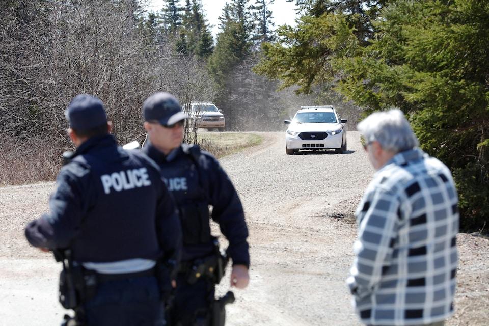 Un citoyen s'approche de deux agents alors que des voitures de police bloquent un chemin de gravier.