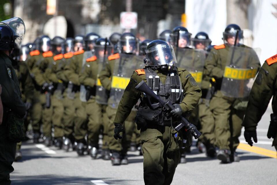 Des policiers en uniforme vêtus de masques à gaz.