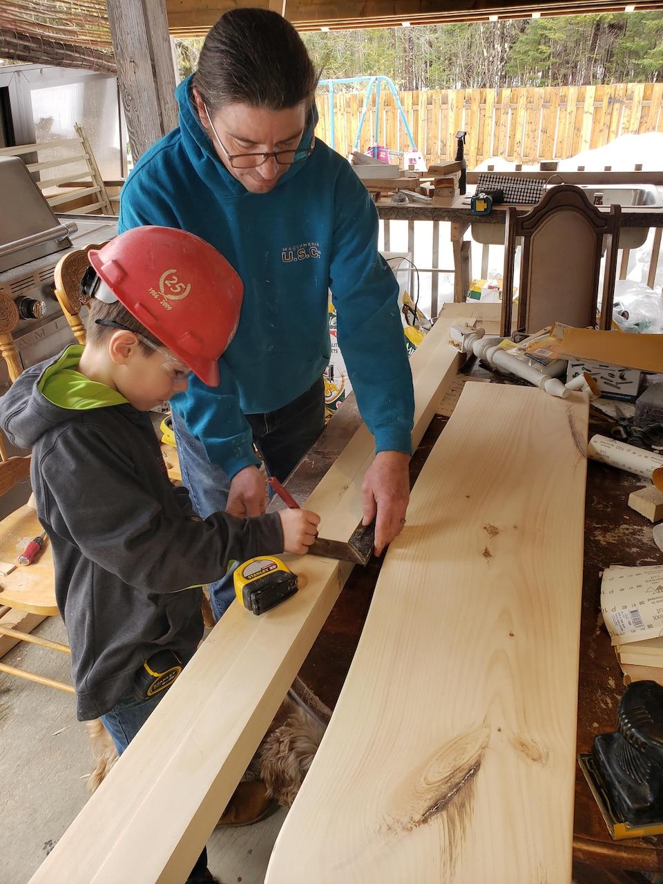 Le père et son enfant devant des planches de bois. Le petit mesure une planche.