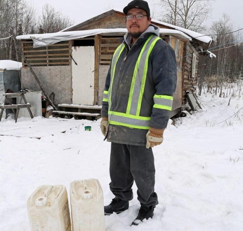 Un homme, Andrew Flett, se tient devant une maison en mauvais état.