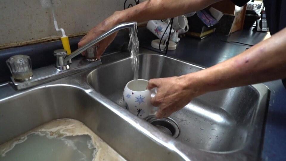 Une main actionne un robinet pour faire couler l'eau dans une tasse.