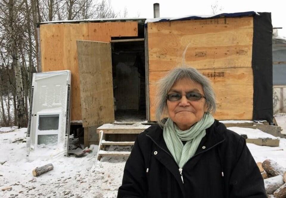 Une femme se tient devant sa maison qui est en mauvais état.