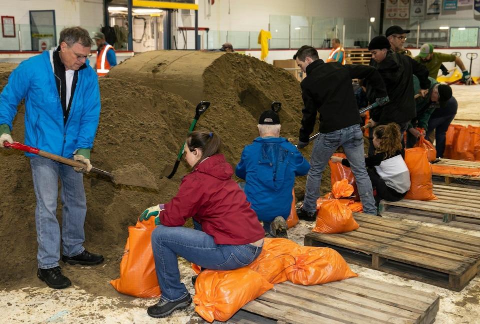 Des gens remplissent des sacs de sable.