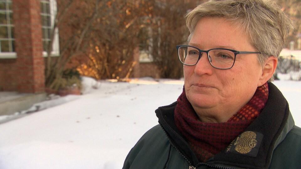Geneviève Tellier répond aux questions d'une journaliste à l'extérieur en hiver.
