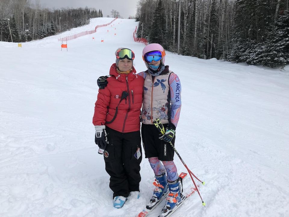 Une skieuse et son entraîneuse au bas d'une piste de ski.