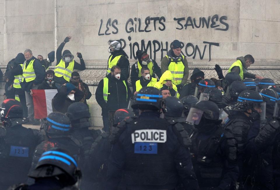 Des manifestants portant des gilets jaunes et des masques font face à des policiers au pied de l`Arc de triomphe.