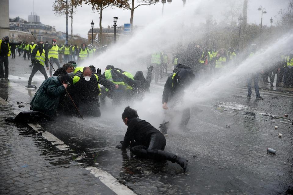 Des manifestants repoussés au sol par un canon à eau.