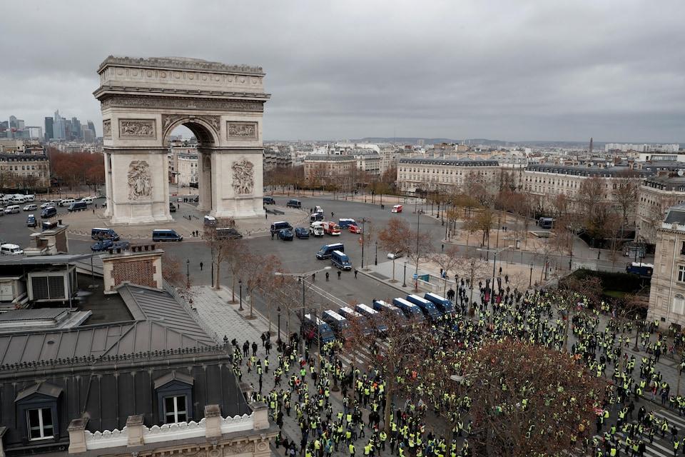 Vue sur l'Arc de triomphe avec un cordon de policiers antiémeutes et des véhicules, en face plusieurs «gilets jaunes».