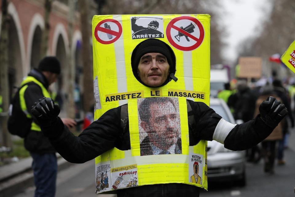 Un manifestant porte un costume en carton jaune sur lequel il est écrit: «Arrêtez le massacre».