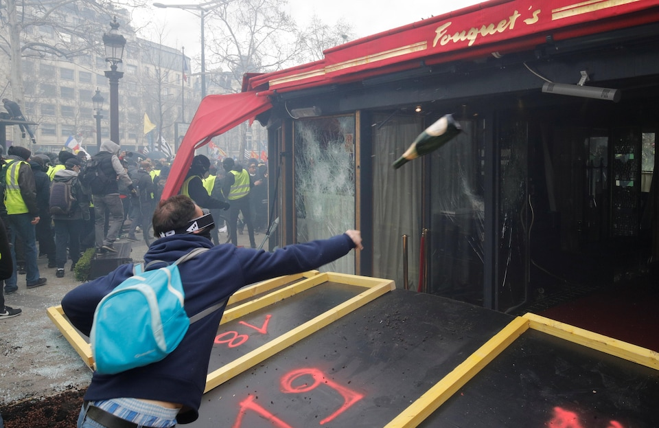 Un casseurs lancent une bouteille contre les vitres du Fouquet's.