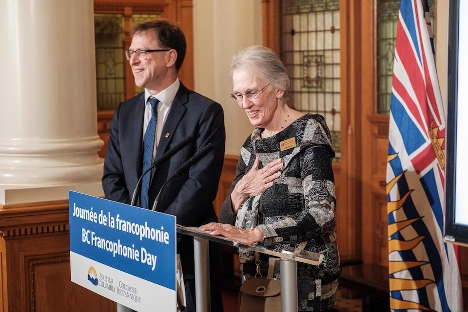 Gisèle Samson s'exprime devant le public à côté du ministre de la Francophonie, Adrian Dix.