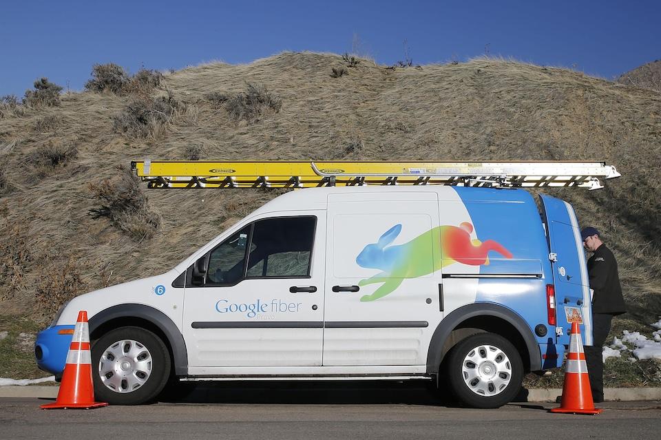 Un technicien de Google Fiber en train de prendre du matériel dans sa camionnette.