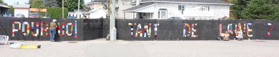 La phrase «Pourquoi tant de laine?» est écrite avec des pièces de tricot sur une clôture noire.