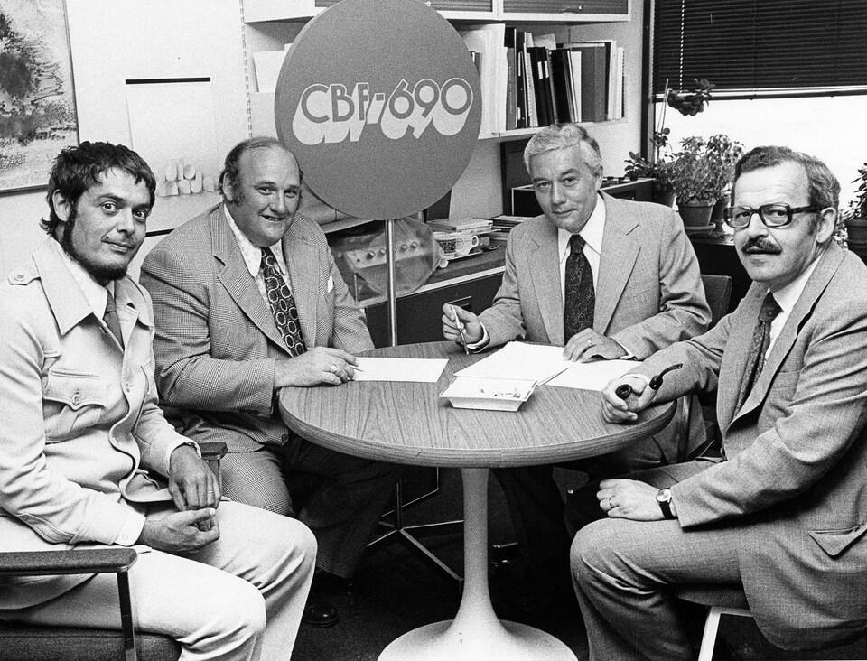 Quatre hommes assis dans un bureau s'apprêtent à signer un document.