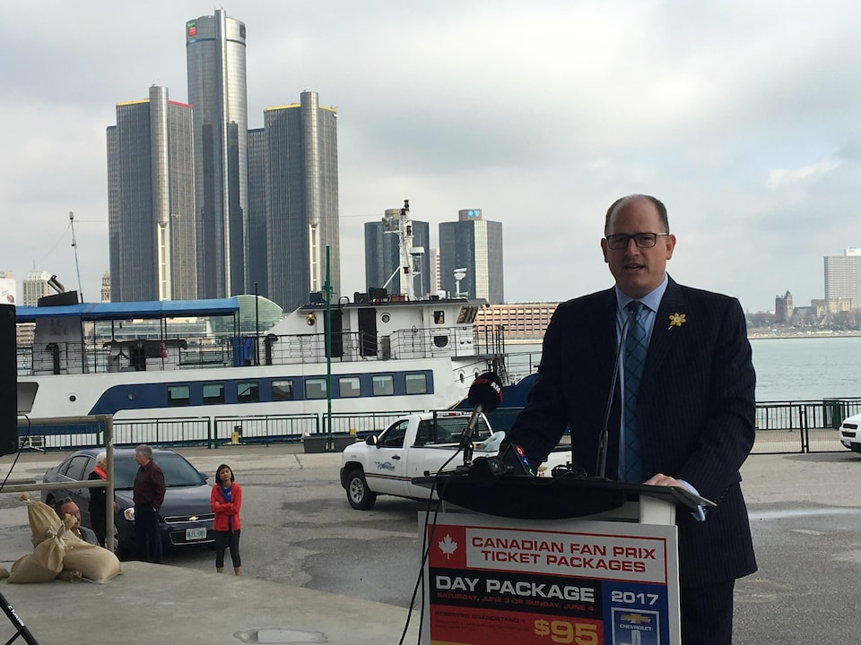 Le maire Drew Dilkens parle à un podium avec des gratte-ciels de Détroit en arrière-plan.