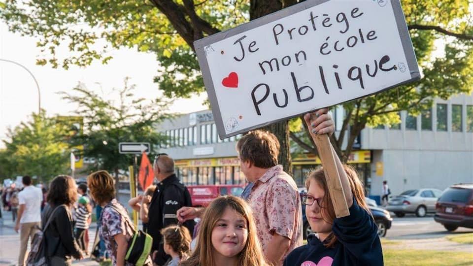 Une jeune fille tient une pancarte sur laquelle est écrit : «Je protège mon école publique». On peut voir de nombreuses personnes former une chaîne humaine en arrière-plan.