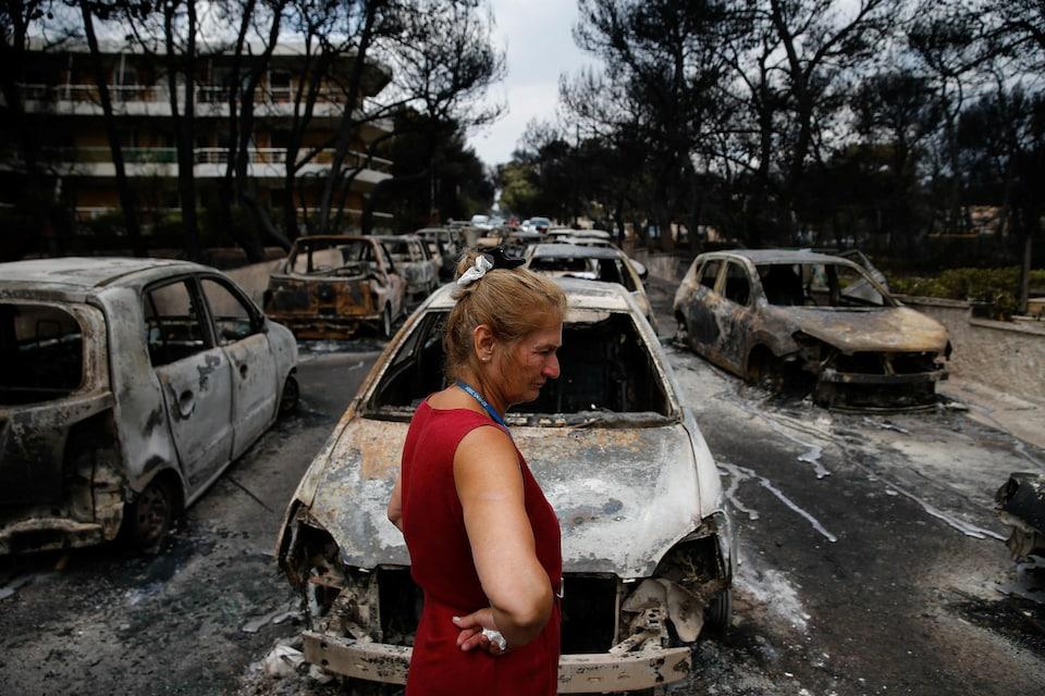 Le 24 juillet 2018, une femme, qui tient un mouchoir dans ses mains, regarde plusieurs voitures brûlées autour d'elle, l'air grave. Ses mains sont posées sur ses hanches.