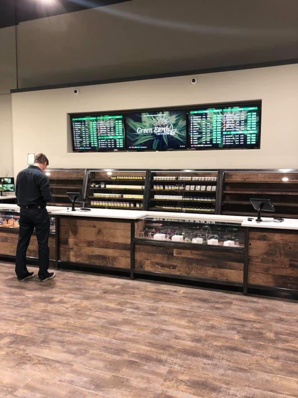 Un client regarde des produits de marijuana pendant qu'il est debout devant un comptoir de la boutique Green Earth Cannabis à Calgary