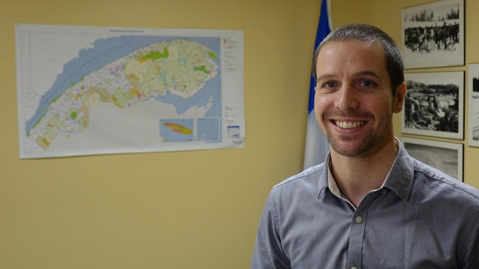 Greg St-Hilaire devant une carte du Bas-Saint-Laurent