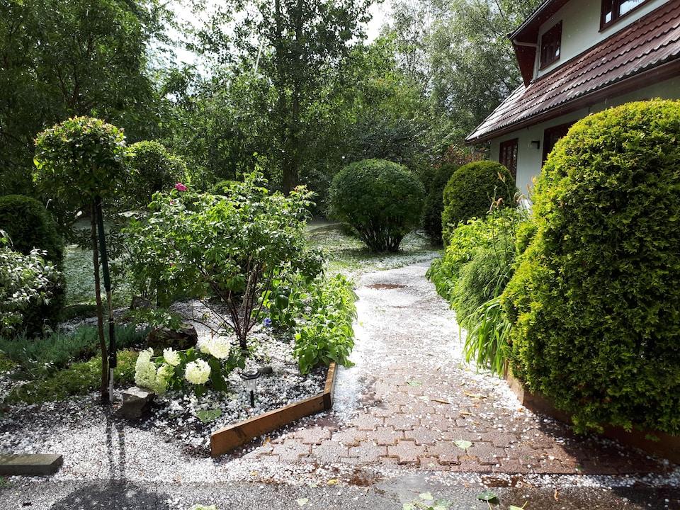 Le sol recouvert de grêlons derrière une résidence