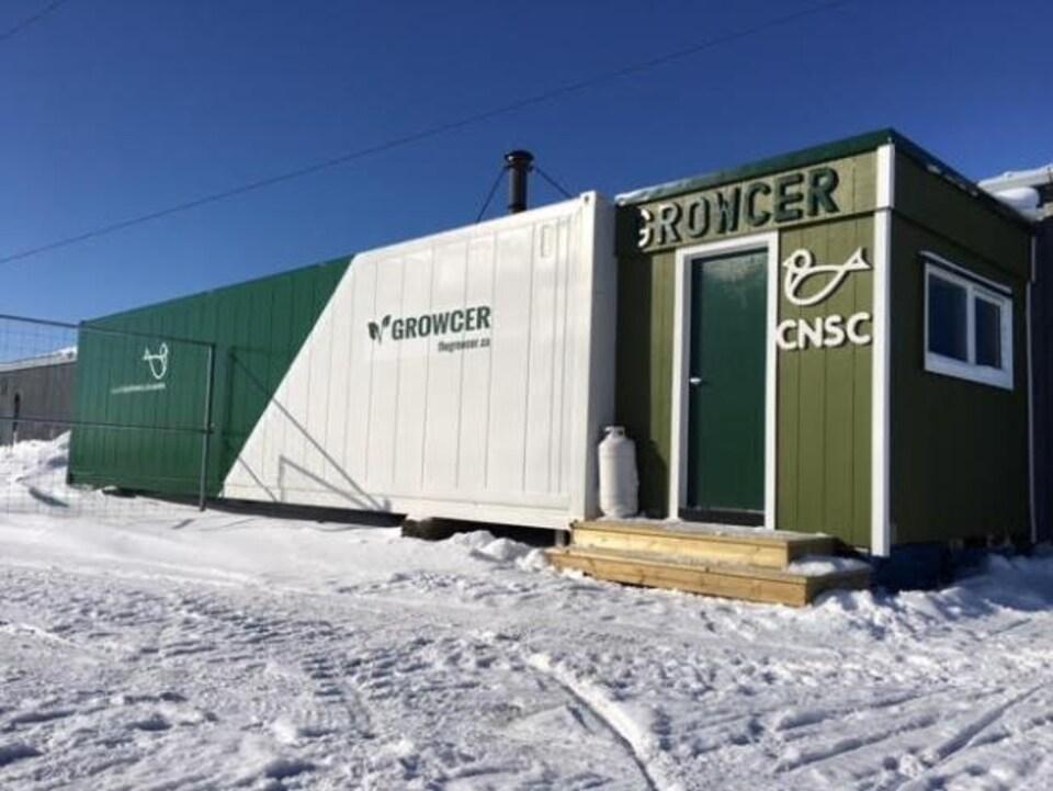 Conteneur rectangulaire blanc et vert autrefois utilisé pour la livraison, qui est maintenant une ferme hydroponique.
