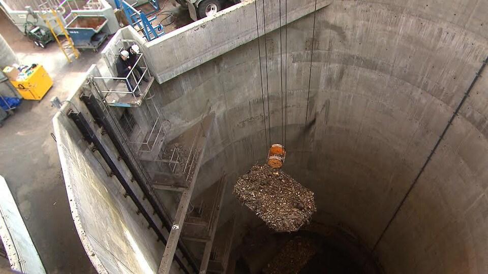 Une grue équipée d'un tamis récupère les gros déchets des égouts.